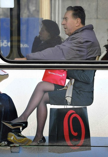 A man sits on bus with an advert for a clothes store in Ljubljana